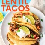 """Overhead of a plate full of three vegetarian tacos on a kitchen linen with fresh lime and cilantro. A text overlay reads, """"Meatless Lentil Tacos."""""""