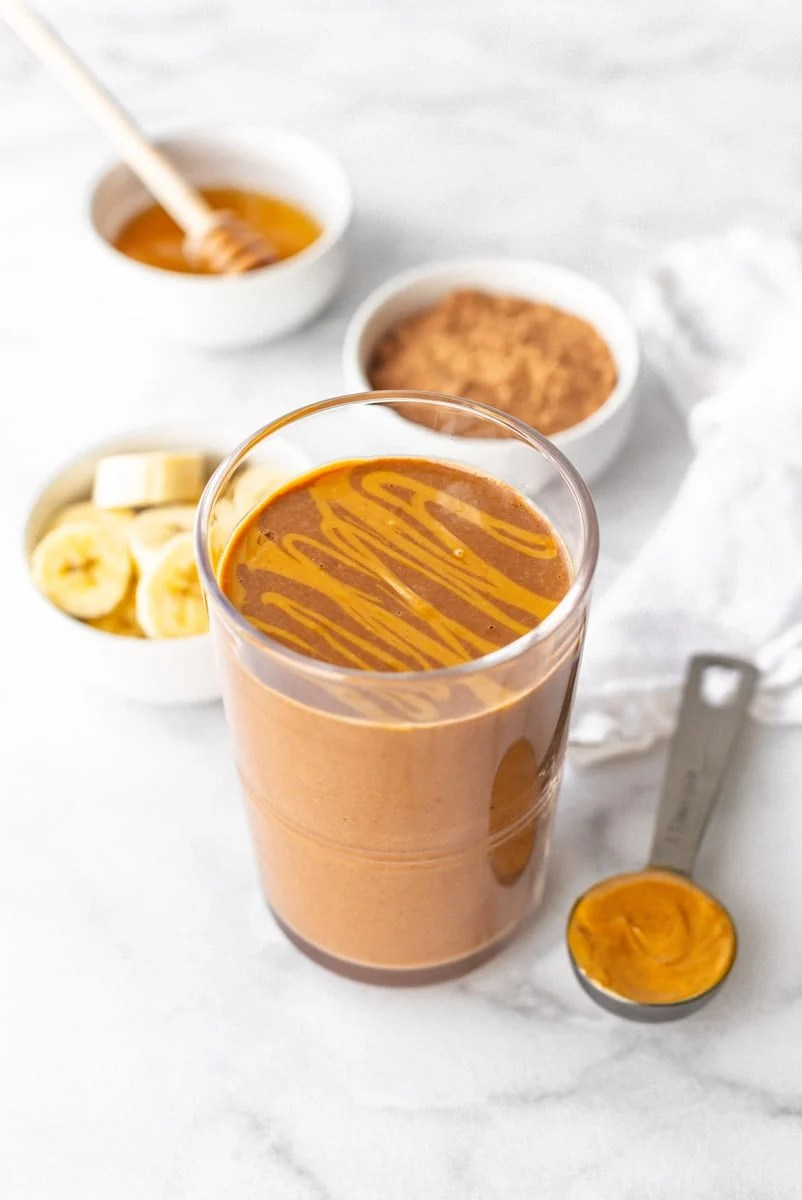 Finished smoothie in a glass with a peanut butter drizzle on top sit in front of small dishes filled with smoothie ingredients.