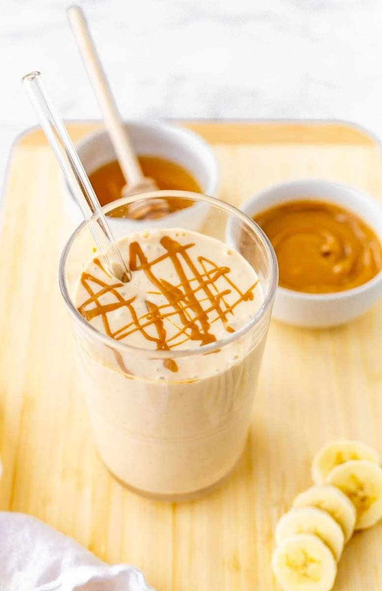 Peanut butter banana smoothie with a peanut butter drizzle on top and banana slices alongside.