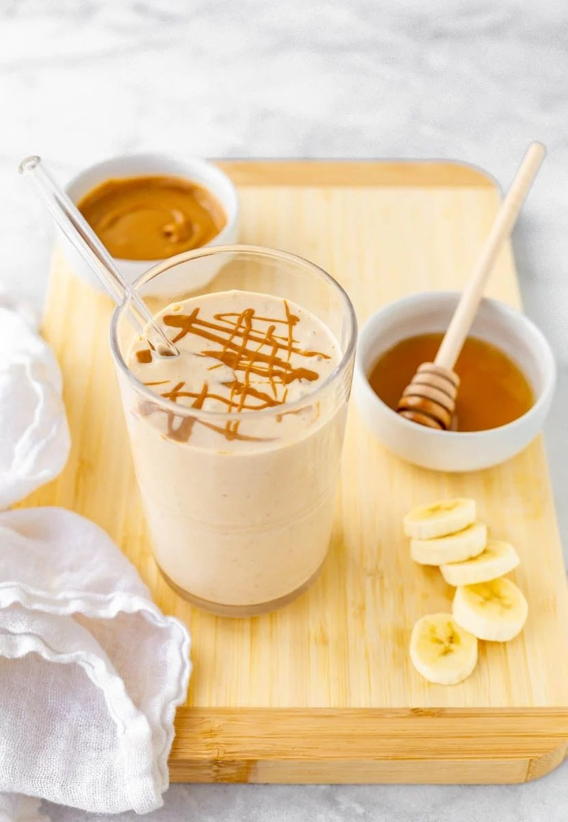 Overhead of smoothie on a cutting board with peanut butter, honey, and banana slices.