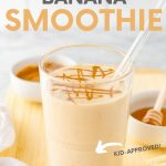 """Close-up of smoothie with glass straw on cutting board with fresh ingredients. A text overlay reads, """"Peanut Butter Banana Smoothie. Kid-Approved!"""""""