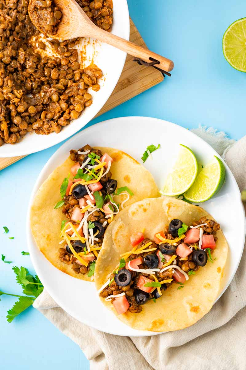 Overhead of two vegetarian tacos on a white plate with lime wedges and fresh cilantro.