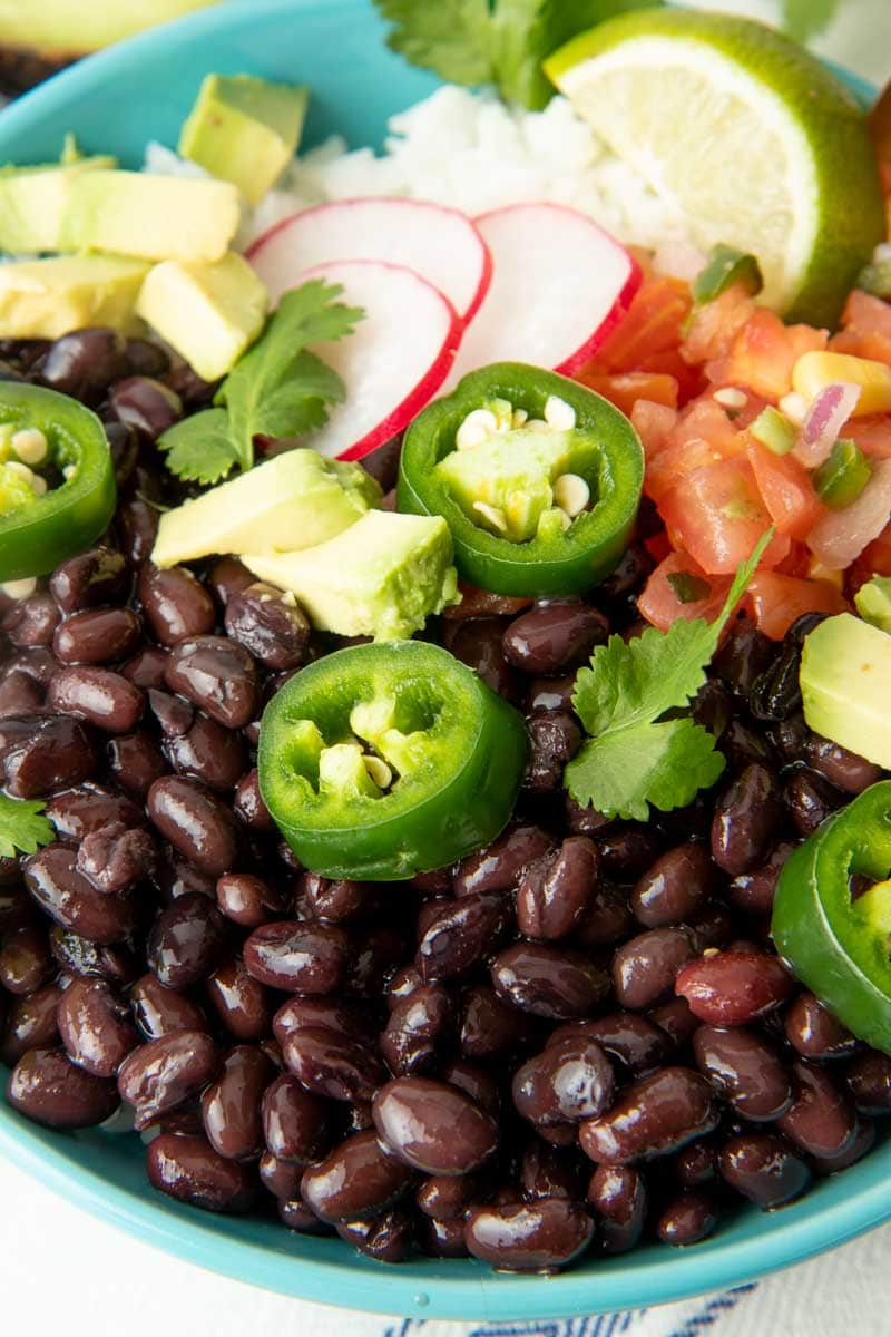 Close up of black beans in a bowl with fresh toppings such as radish slices, jalapeno slices, and avocado.