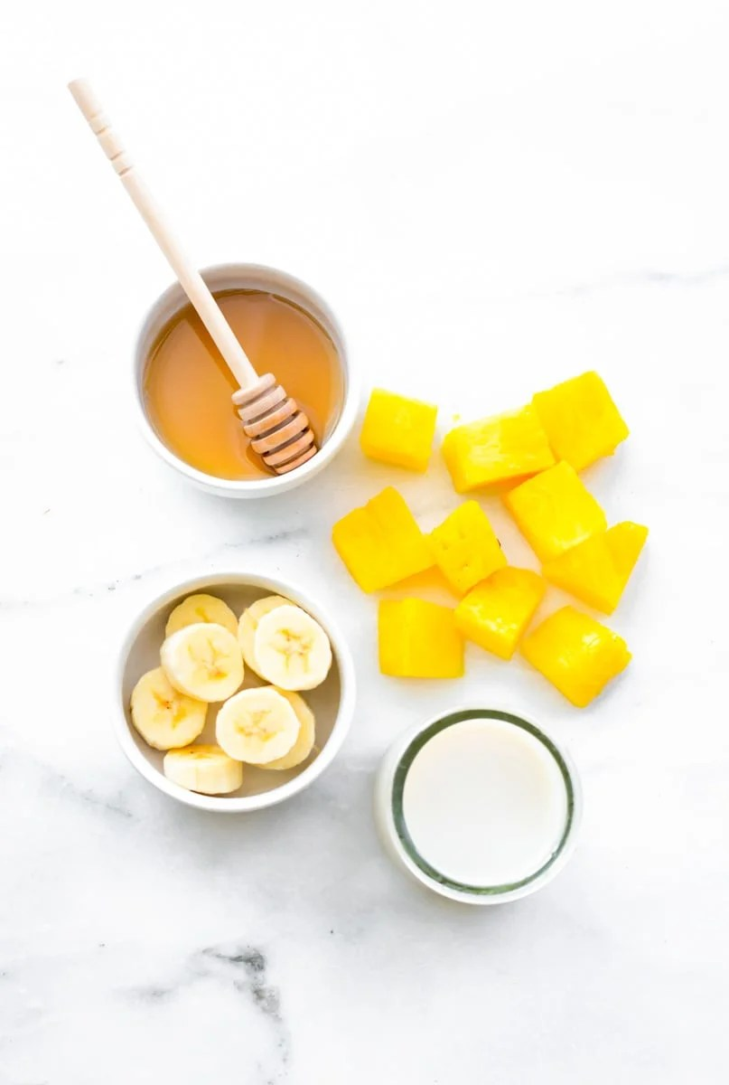 Overhead of four ingredients needed for coconut pineapple smoothie recipe.