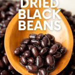 "Seasoned black beans rest on a wooden spoon in a large pot of cooked beans. A text overlay reads, ""How to Cook Dried Black Beans."""