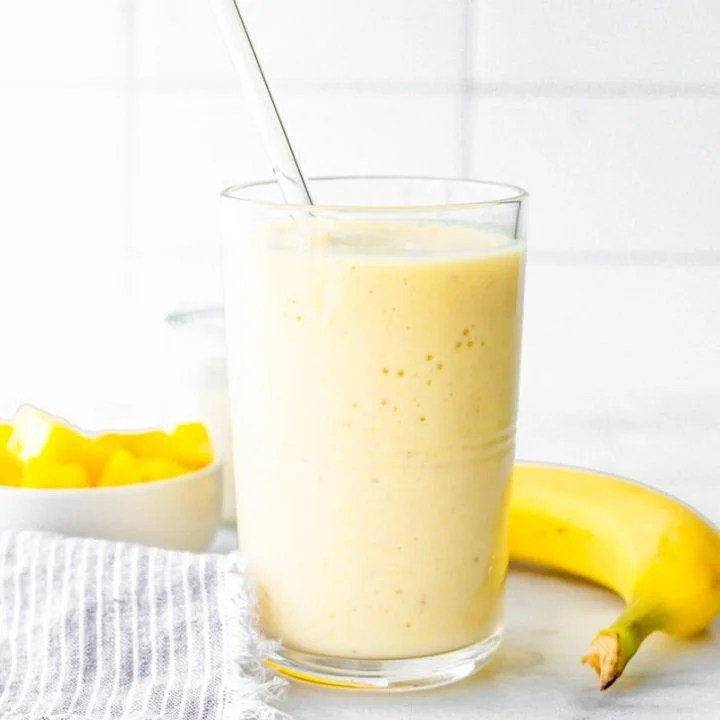Coconut pineapple smoothie with a glass straw on a counter with fresh pineapple and banana.