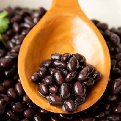 Seasoned black beans rest on a wooden spoon in a large pot of cooked beans.