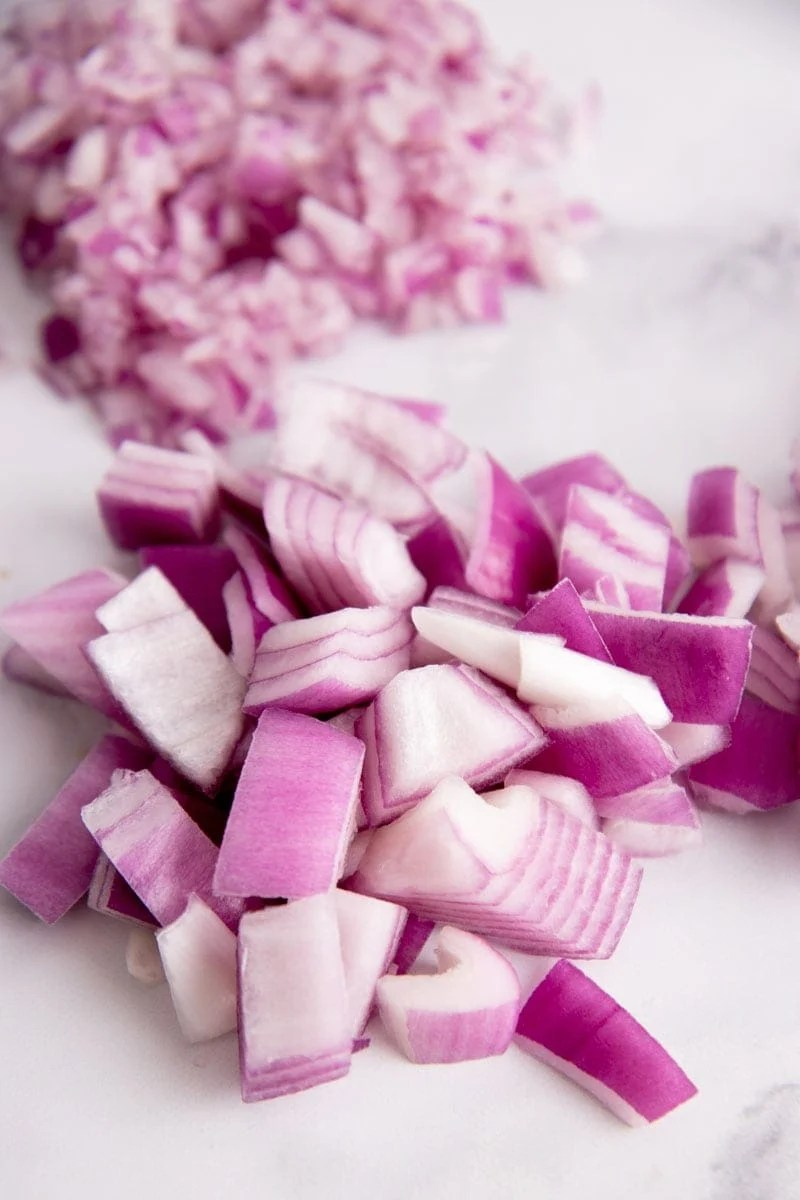 Chopped red onion in a pile with minced red onion in a pile behind.