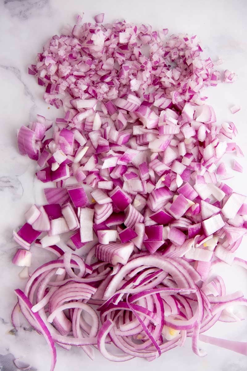 Overhead of long rows of minced, diced, chopped, and sliced red onions laid out from top to bottom.