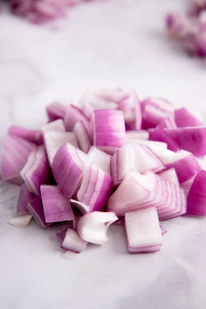 Close-up of a pile of chopped red onion on a white marble countertop.