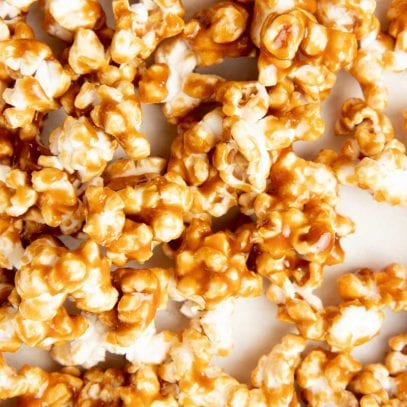 Overhead of caramel popcorn on a white counter.