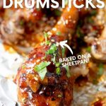 """Close-up of a sticky chicken drumstick garnished with chopped fresh cilantro on a foil lined sheet pan. A text overlay reads, """"Sticky Chicken Drumsticks. Baked on a Sheetpan!"""""""