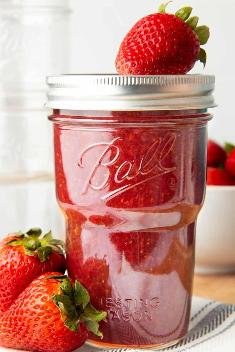 Strawberry jam in a closed and capped jar. A fresh strawberry sits on top of the lid, and two more berries are next to the jar.