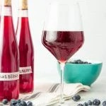 A stemmed wine glass filled with chilled blueberry wine stands surrounded by fresh blueberries and two bottles of homemade wine.