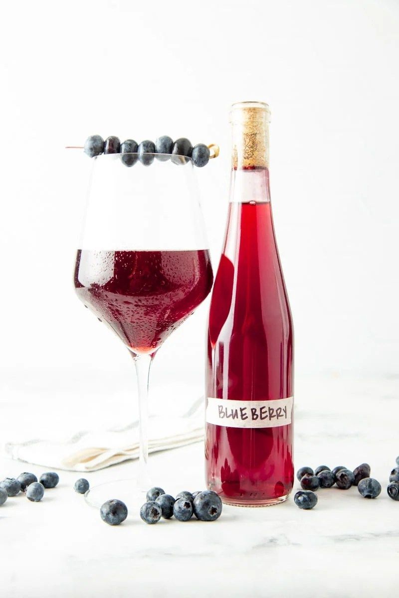 A chilled glass of blueberry wine with a cocktail skewer of fresh blueberries across the rim stands next to a bottle of homemade wine.