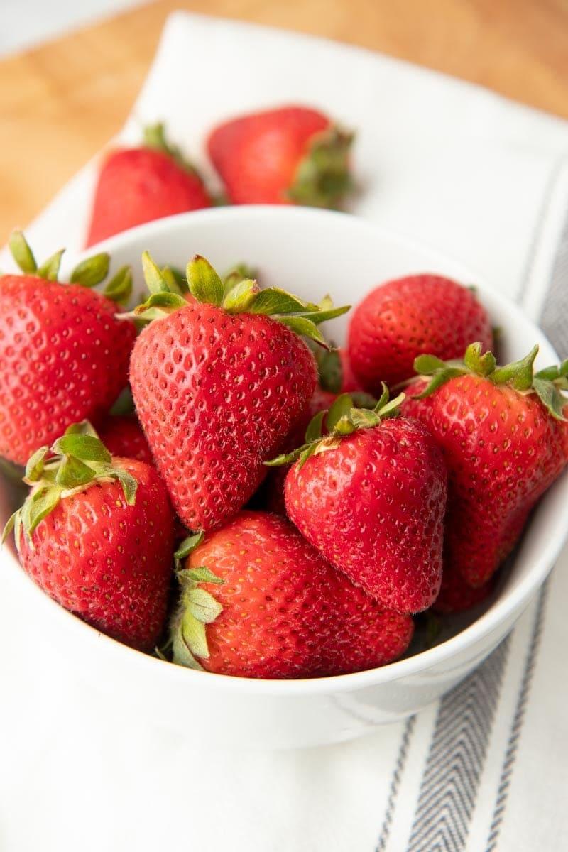 Fresh strawberries fill a white bowl