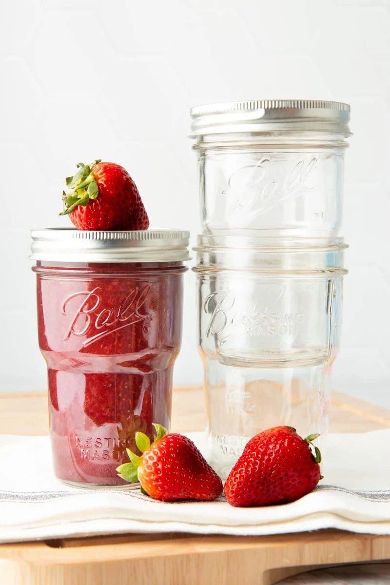 Strawberry jam in a glass jar sits next to two nested glass jars