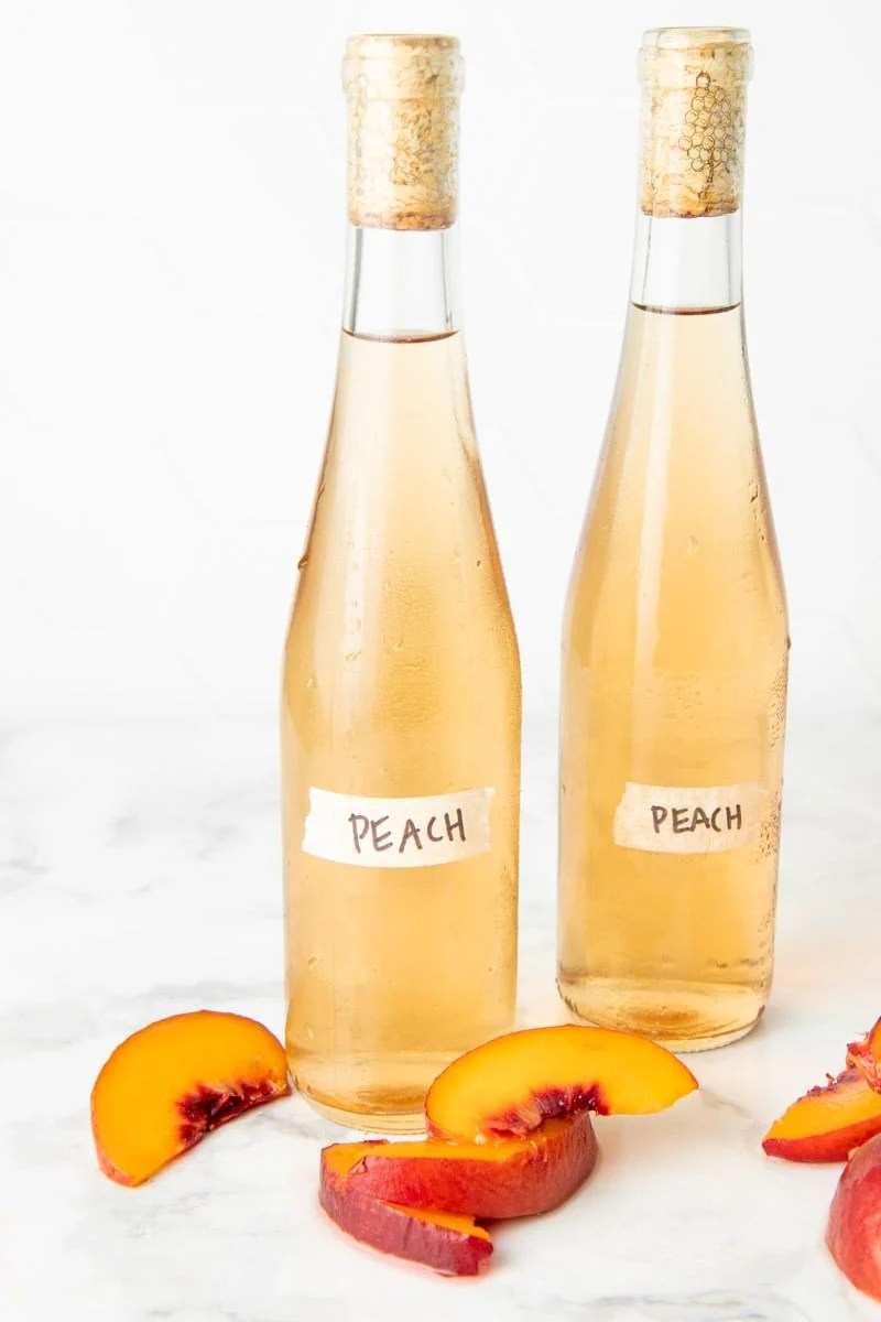 Close up of two bottles of homemade peach wine and fresh peach slices.