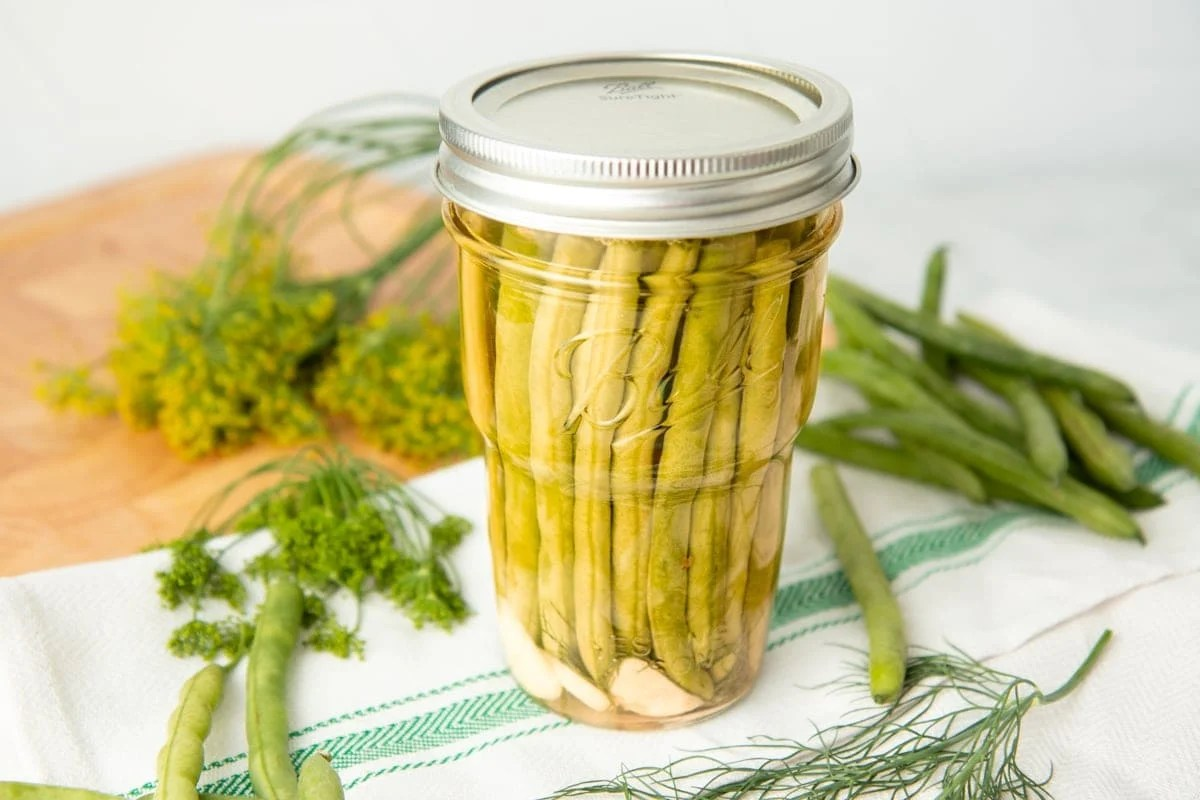 Canned dilly beans in a pint jar, with fresh green beans and dill surrounding the jar