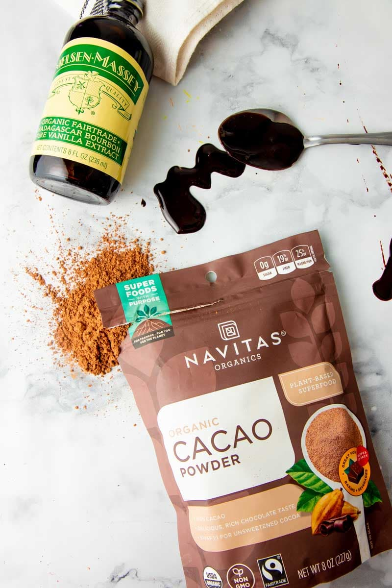 Overhead of fairtrade ingredients such as Nielsen-Massey vanilla extract and Navitas Organics cacao powder on a white marble countertop.