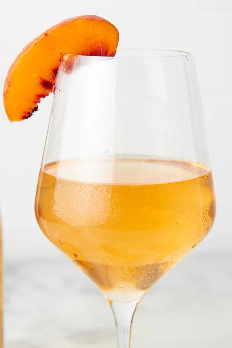 Close up of a glass of chilled, clear peach wine with a fresh peach slice on the rim.