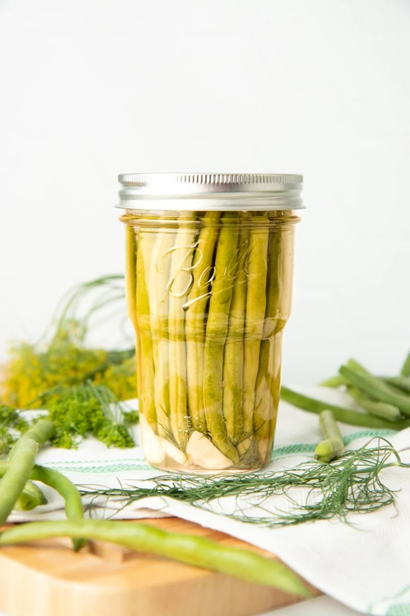 A jar of pickled dilly beans sits on a tea towel on top of a wooden cutting board. Fresh dill and additional beans are around the jar.
