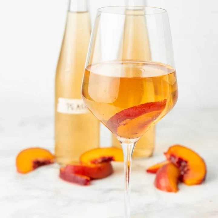 A glass of wine stands in front of two bottles and fresh peach slices.