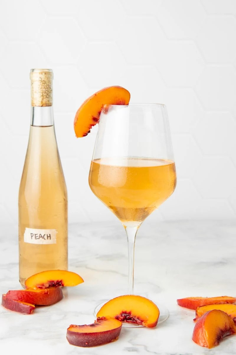 A chilled glass of homemade country wine stands with fresh peach slices around it, and a full bottle behind it.