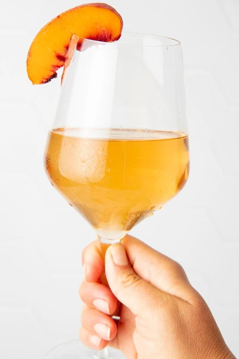 A hand holds up a chilled glass of homemade peach wine.