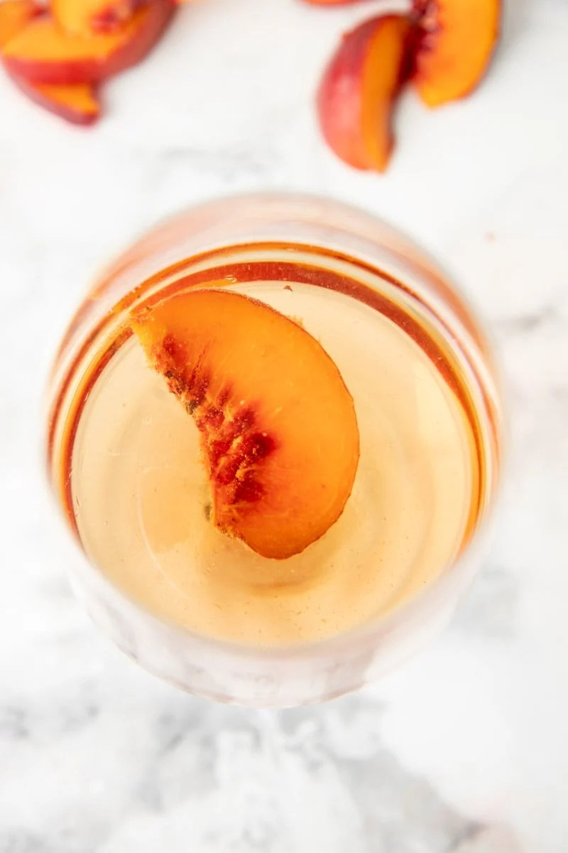 Overhead of clear peach wine in a glass with a fresh peach slice.
