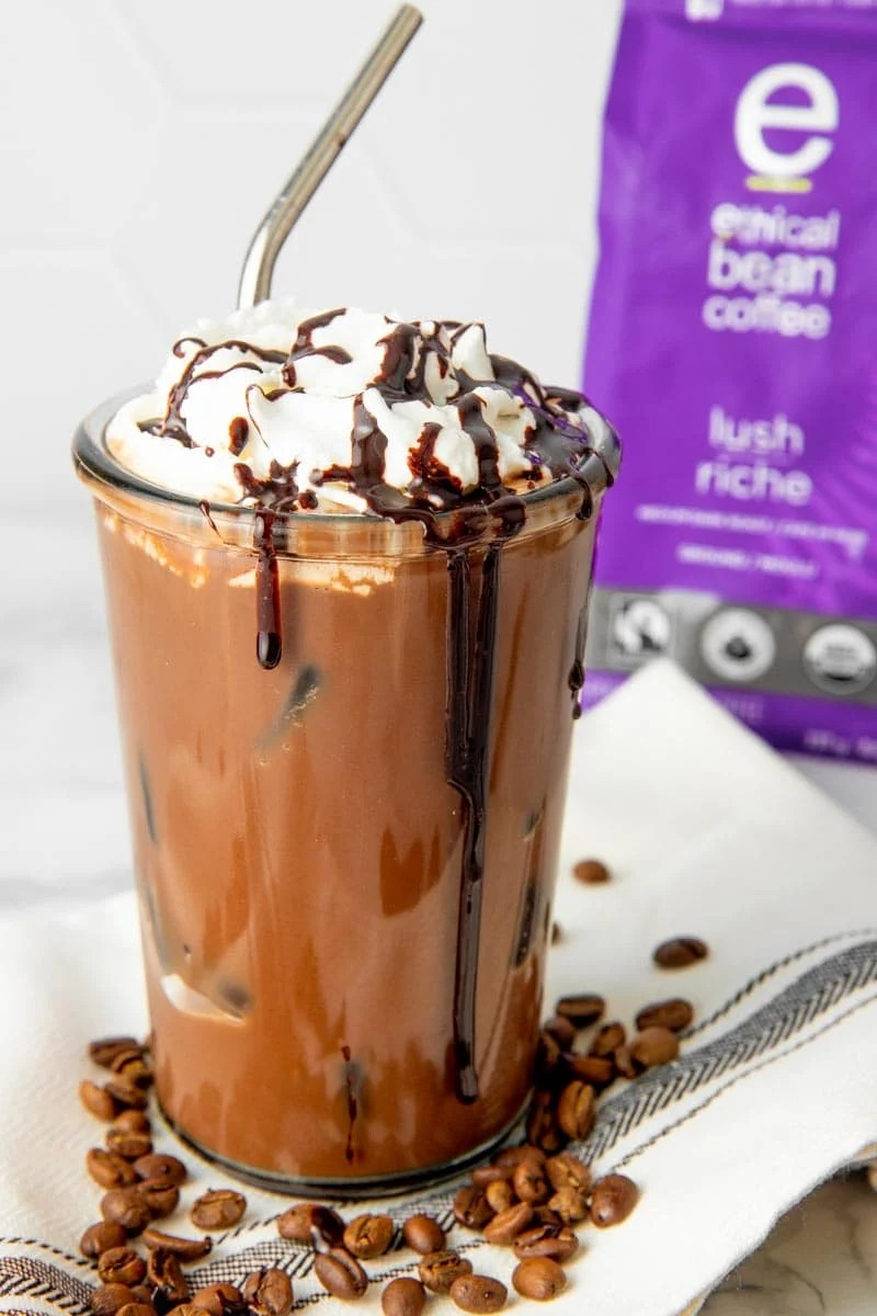 A homemade iced mocha garnished with whipped cream and diy mocha syrup drizzles sits in front of a bag of fairtrade coffee.