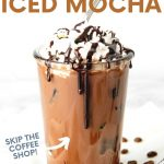 """Close-up of homemade iced mocha in a glass with ice garnished with whipped cream and a mocha syrup drizzle. A text overlay reads """"Homemade Iced Mocha. Skip the Coffee Shop!"""""""