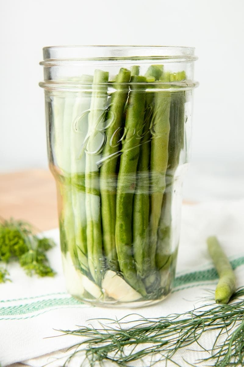 Jar packed with green beans and garlic