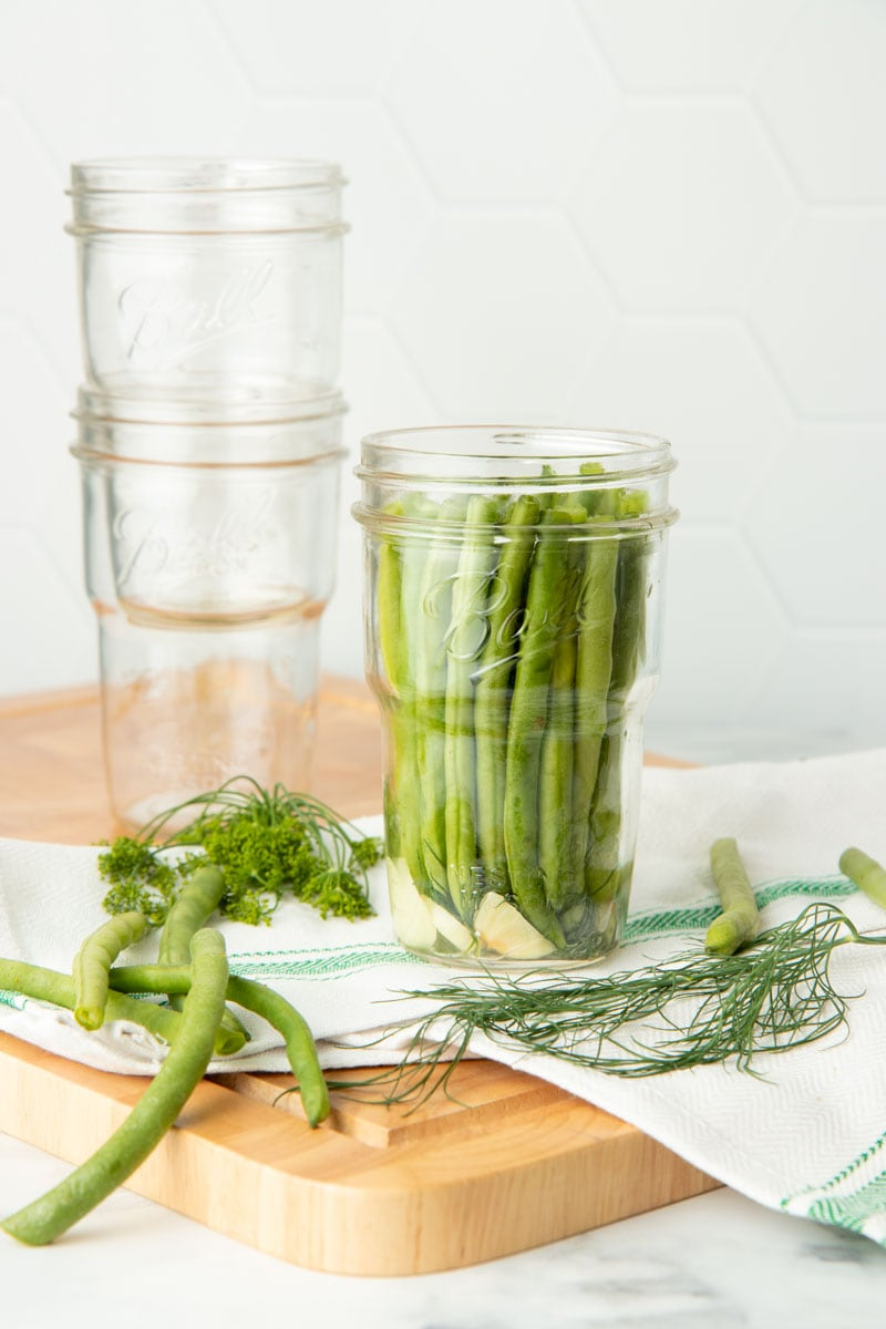 Green beans are packed into a glass jar. Two empty glass jars are nested behind the full jar.