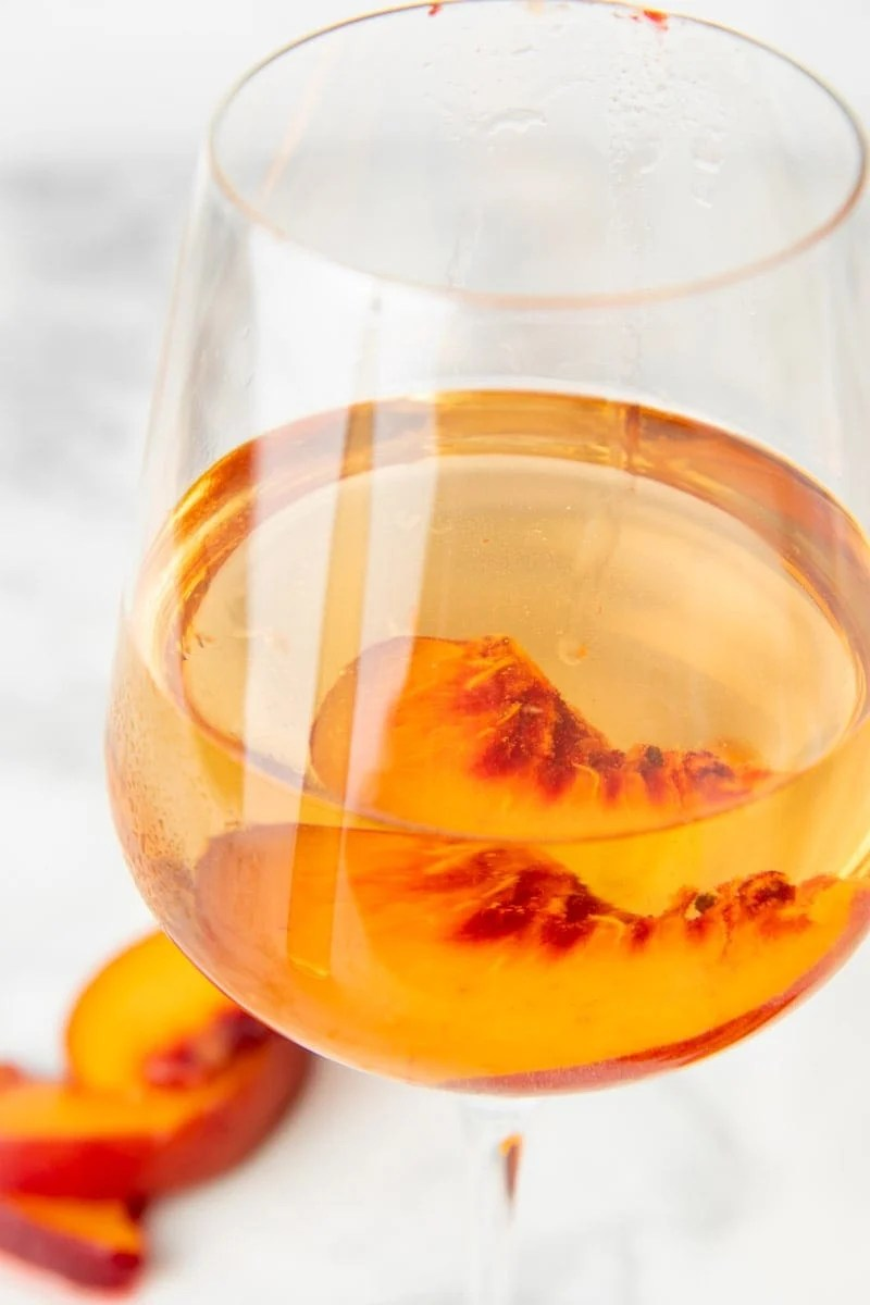 Close up of a glass of peach wine with a fresh peach slice in the glass.