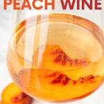 """Close up of a glass of peach wine with a fresh peach slice in the glass. A text overlay reads, """"How to Make Peach Wine."""""""