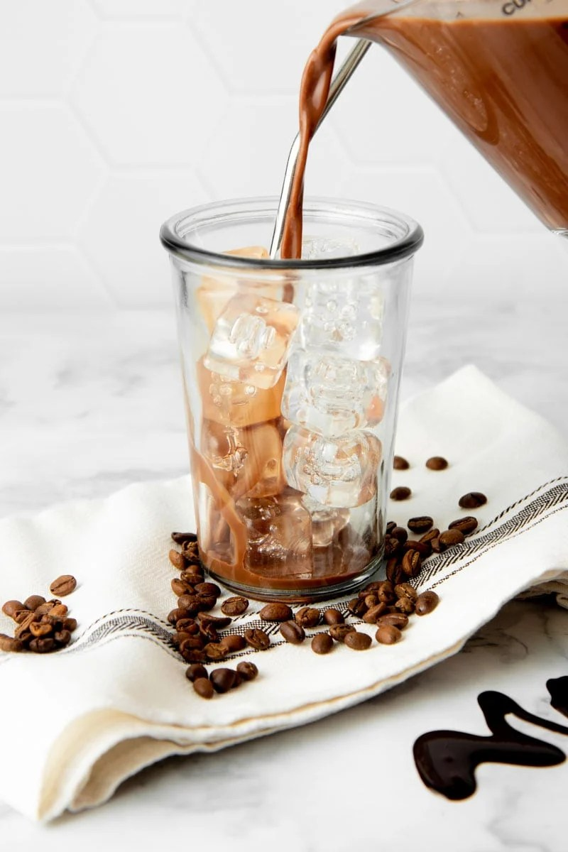 Pouring chilled mocha into a glass with ice.