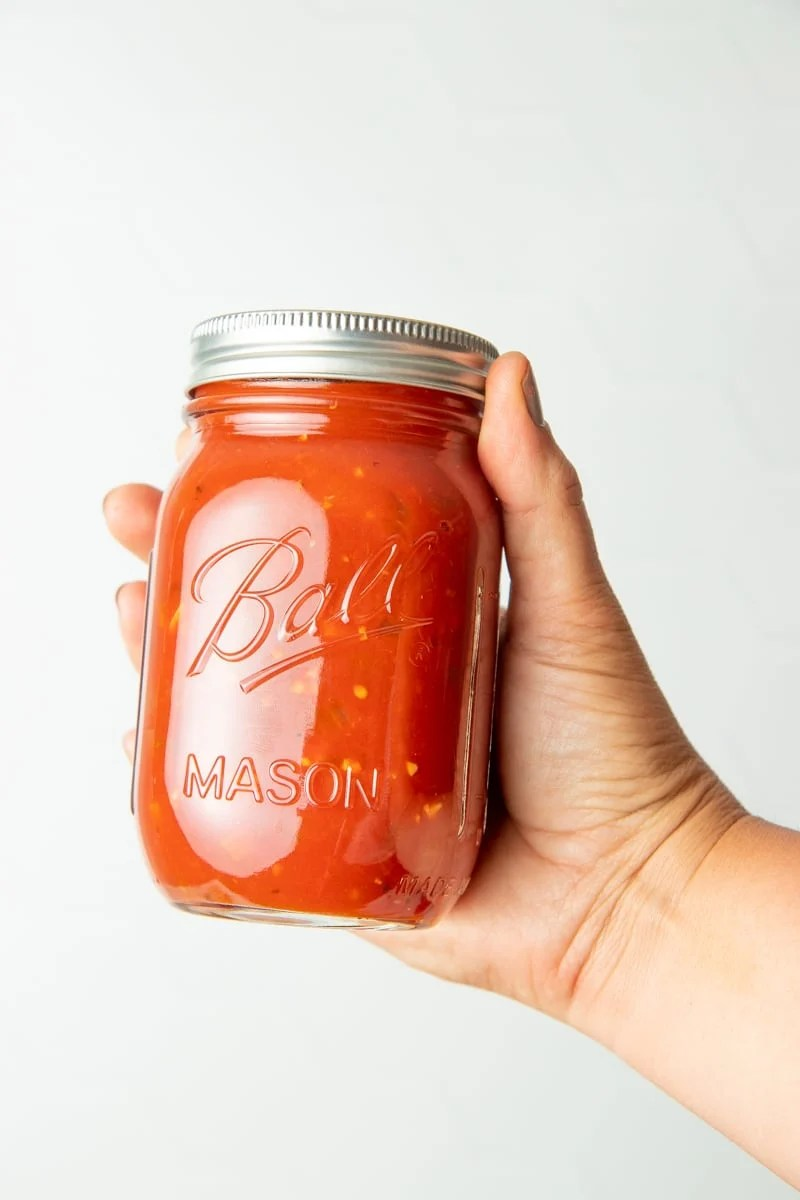A hand holds out a jar of homemade spaghetti sauce