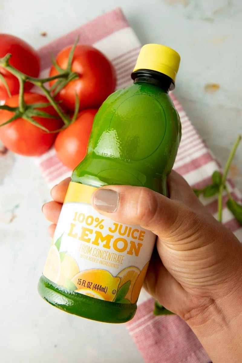 A hand holds out a bottle of lemon juice