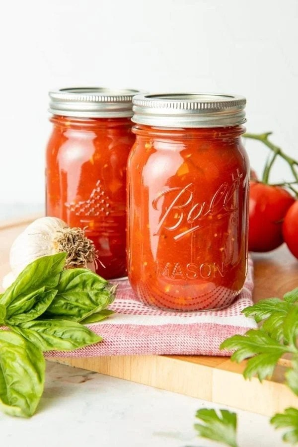 Two full canning jars of spaghetti sauce surrounded by fresh garlic, tomatoes, and herbs.