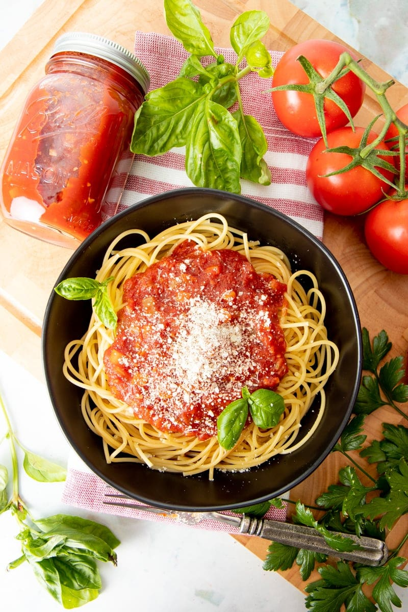 A black bowl is filled with spaghetti, sauce, and basil. The bowl is surrounded by fresh herbs, fresh tomatoes, and a jar of sauce.