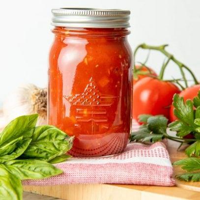 A full glass jar of spaghetti sauce sits on a dish towel on a cutting board.