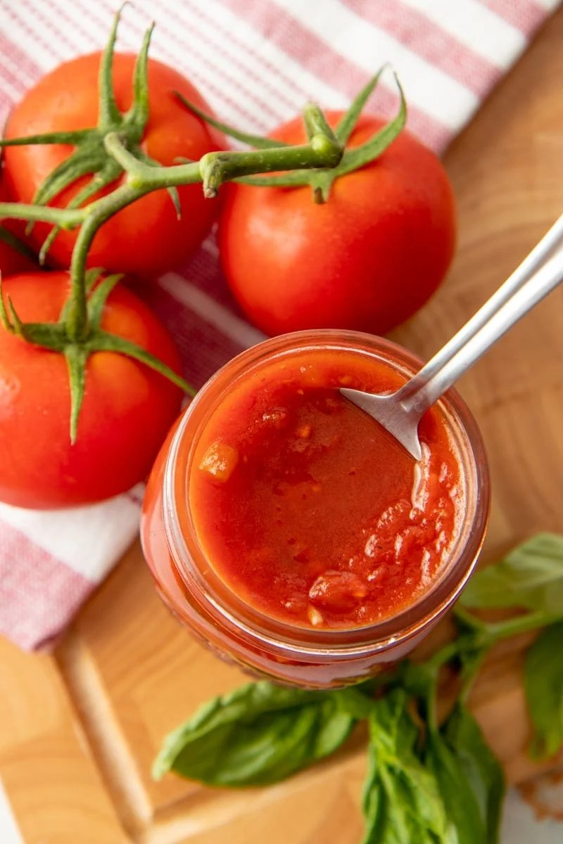 A spoon dips into a jar of spaghetti sauce.