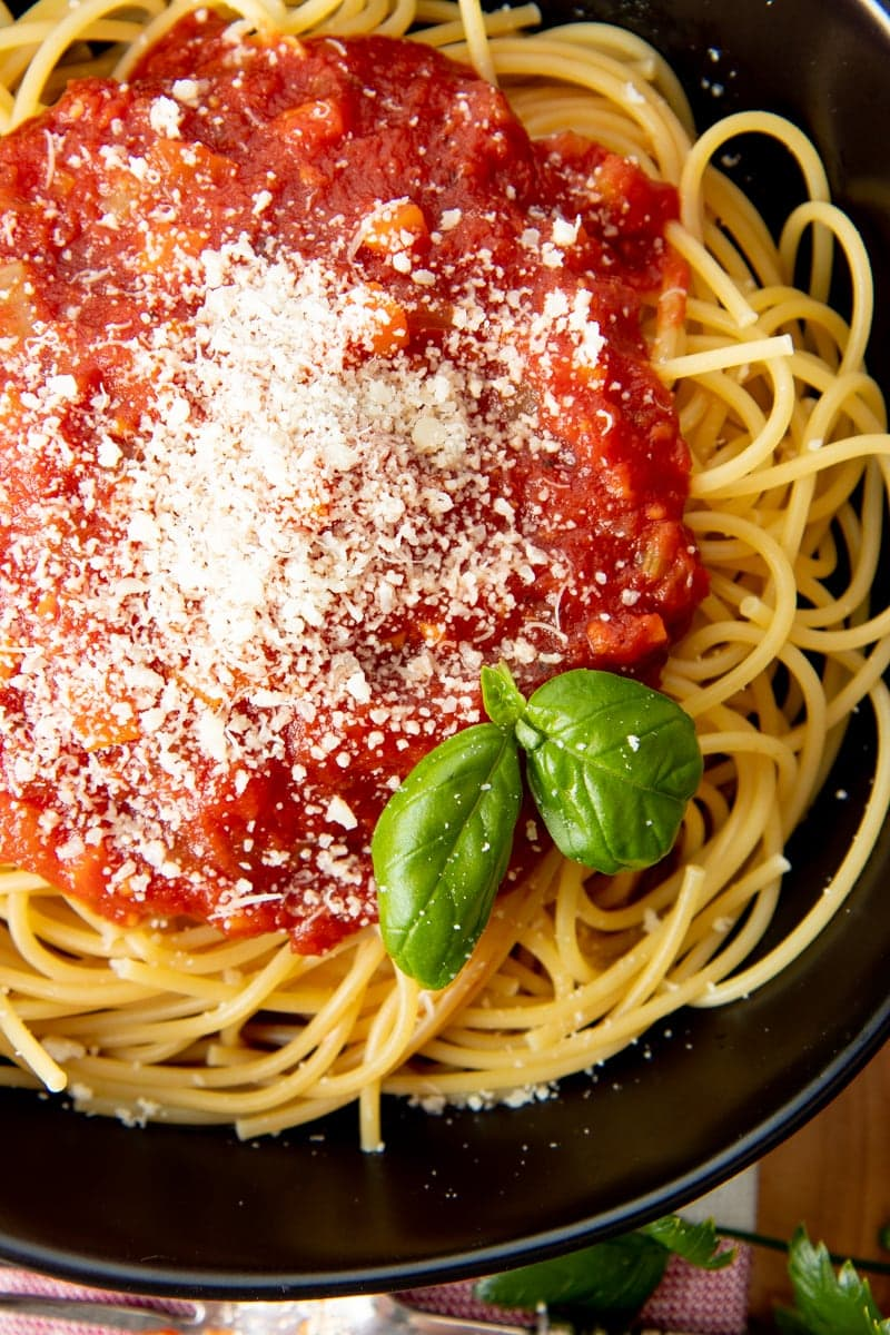 A black bowl is filled with spaghetti, topped with sauce and fresh basil