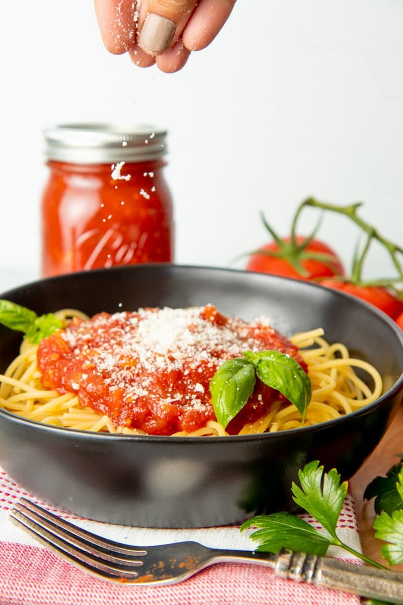 A hand sprinkles Parmesan over a bowl of spaghetti with sauce and basil