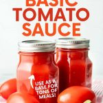 """Close-up of two jars of canned tomato sauce with fresh tomatoes and basil. A text overlay reads, """"How to Can Basic Tomato Sauce. Use As a Base for Tons of Meals!"""""""