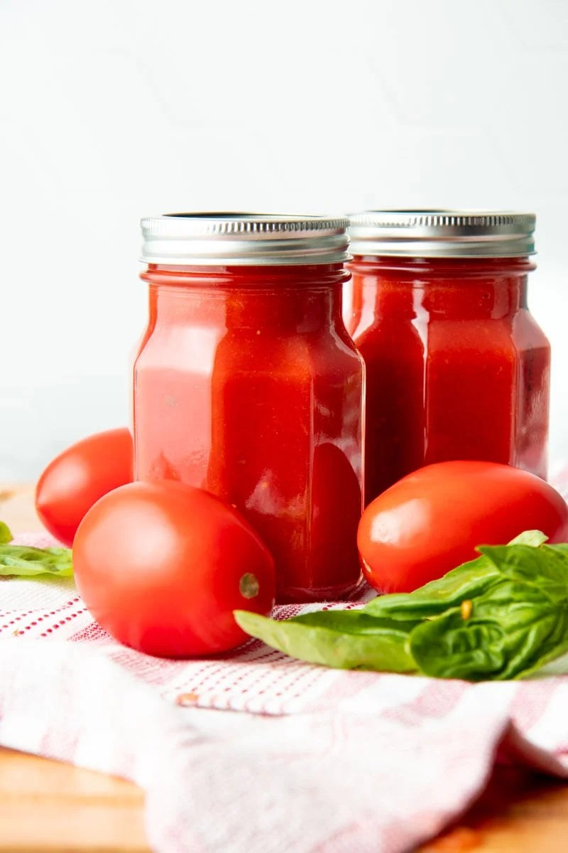 Two finished jars of basic sauce with fresh roma tomatoes and basil.