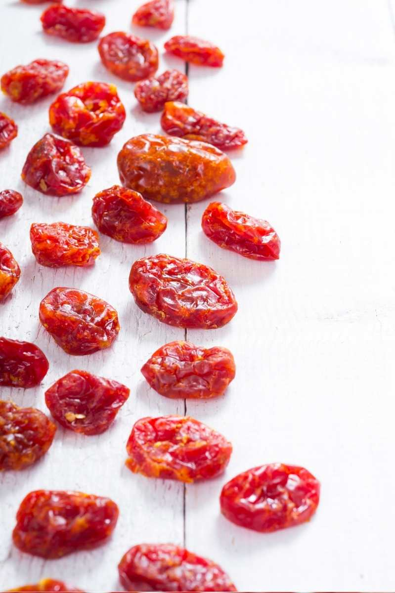 Dried grape tomatoes on a wooden countertop.