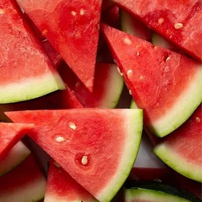 Overhead of seedless watermelon wedges stacked into a pile.