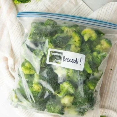 """A full freezer bag labeled """"Broccoli!"""" rests on a kitchen linen."""